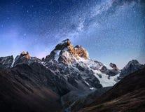 Cielo stellato fantastico Paesaggio di autunno e picchi innevati Cresta caucasica principale Mountain View dal supporto Ushba Mey fotografia stock libera da diritti