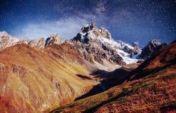 Cielo stellato fantastico Paesaggio di autunno e picchi innevati Cresta caucasica principale Mountain View dal supporto Ushba Mey Immagini Stock Libere da Diritti