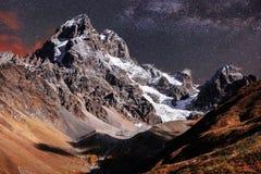 Cielo stellato fantastico Paesaggio di autunno e picchi innevati Cresta caucasica principale Mountain View dal supporto Ushba Mey Immagine Stock Libera da Diritti