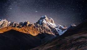 Cielo stellato fantastico Paesaggio di autunno e picchi innevati Cresta caucasica principale Mountain View dal supporto Ushba Mey Fotografia Stock