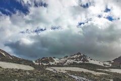 Cielo tenebroso Un turista solo sale la collina lungo il fiume Fotografia Stock