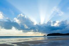 Cielo tropical de la puesta del sol de la playa con las nubes encendidas Foto de archivo