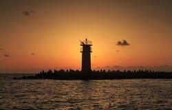 Cielo vibrante hermoso de la salida del sol sobre la agua de mar tranquilo y el faro Fotos de archivo libres de regalías