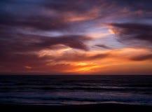 Cielo vivo, dramático sobre el mar en la puesta del sol con pendiente anaranjada azul y nubes oscuras foto de archivo libre de regalías