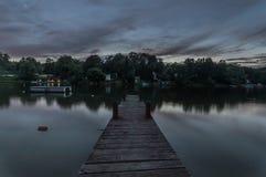 Cielo y muelle oscuros en un lago fotografía de archivo libre de regalías