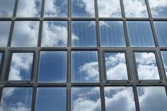 Cielo y nubes reflejados en ventanas del edificio foto de archivo