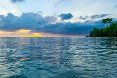 Cielos amarillos, anaranjados, rosados, azules iluminados como rayos solares estallados a través de las nubes en la puesta del so imágenes de archivo libres de regalías