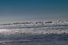 Cielos azules claros y luz del sol con las ondas de Oc?ano Atl?ntico que se estrellan sobre la playa de la arena sin gente en Aga foto de archivo libre de regalías