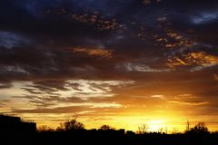 Cielos coloridos de la puesta del sol en una pequeña ciudad imagen de archivo