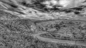 Cielos tempestuosos Curvar la carretera Montañas y valles soledad foto de archivo libre de regalías