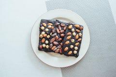 Ciemna czekolada, odizolowywająca na bielu z całymi dokrętkami Zdjęcie Stock