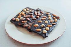 Ciemna czekolada, odizolowywająca na bielu z całymi dokrętkami Zdjęcie Royalty Free