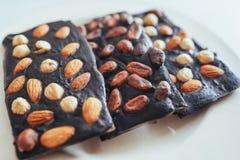 Ciemna czekolada, odizolowywająca na bielu z całymi dokrętkami Obraz Royalty Free