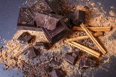 Ciemna czekoladowa sterta, cynamon i kakaowy proszek, Łamani czekolada kawałki i kakaowy proszek na czarnym tle czekoladowy bar c Obraz Stock