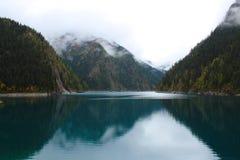 Ciemna góra pod mgłą i chmurą w jeziorze Fotografia Royalty Free
