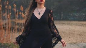 Ciemna królowa na brzeg magiczny jezioro, zła czarownica w modnej czerni sukni z luźnymi koronkowymi rękawami i wysocy rzemienni  zbiory wideo