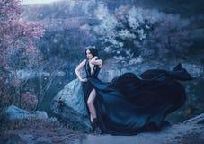 Ciemna królowej poza przeciw tłu ponure skały Luksusowa czerni suknia z długi taborowy trzepotać w zdjęcia royalty free