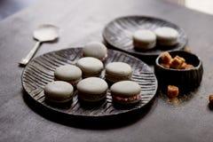 Ciemna monochromatyczna fotografia Popielaci tortów macaroons na ciemnej powierzchni stół obok cukierniczki z i łyżki, Zdjęcie Royalty Free