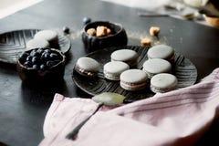 Ciemna monochromatyczna fotografia Popielaci tortów macaroons na ciemnej powierzchni stół obok cukierniczki z i łyżki, Zdjęcia Royalty Free