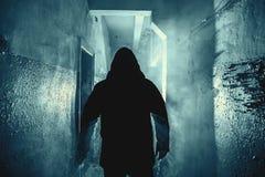 Ciemna sylwetka dziwaczny niebezpieczeństwo mężczyzna w kapiszonie w plecy świetle z dymem lub mgle w strasznym grunge korytarzu, zdjęcia royalty free