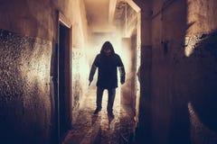 Ciemna sylwetka dziwaczny niebezpieczeństwo mężczyzna z nożem w ręce w strasznym grunge korytarzu, tunelu lub fotografia stock
