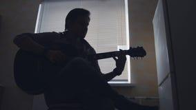 Ciemna sylwetka młody atrakcyjny mężczyzna muzyk komponuje muzykę na gitarze sztukach i, sylwetka zdjęcie stock