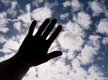 Ciemna sylwetka ręka jest końcowym słońcem na niebieskim niebie z chmurami Zdjęcia Stock