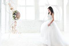 Ciemna z włosami panna młoda w olśniewa białej ślubnej sukni zdjęcia royalty free