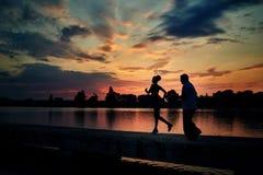 Ciemne sylwetki działająca dziewczyna i starszy mężczyzna podczas gdy zmierzch blisko jeziora obrazy royalty free