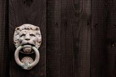 Ciemnego czerni drewniany tło z lwem kształtował drzwiowego knocker i c Obrazy Royalty Free