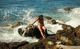 Ciemnego włosy kobieta Siedzi na skałach w Wodnym pośpiechu fotografia royalty free