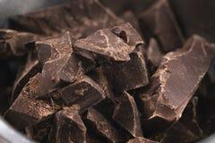 Ciemni czekoladowi kawały w stalowym pucharze na stole Obrazy Royalty Free
