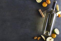 Ciemni kolory, błyszczy światła Butelka otaczająca wyśmienicie i soczystymi owoc na wieśniak powierzchni biały wino Odgórny widok obraz stock