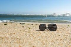 Ciemni okulary przeciwsłoneczni na piaskowatej plaży w lecie, niskiego kąta strzał zdjęcie stock