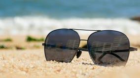 Ciemni okulary przeciwsłoneczni na piaskowatej plaży w lecie, zakończenie w górę zdjęcie royalty free