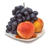 Ciemni winogrona i brzoskwinie na talerzu pojedynczy białe tło Zdjęcia Royalty Free