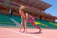 Ciemnoskóra dziewczyny atleta przygotowywa zaczynać na różowej karuzeli z białymi ocechowaniami przeciw tłu puści stojaki z zdjęcia stock