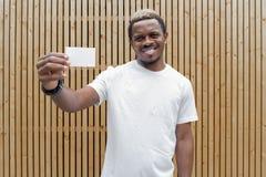 Ciemnoskóry mężczyzna w białej koszulce pokazuje pustą wizytówkę kamera fotografia royalty free