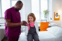 Ciemnoskóry pediatra pokazuje termometr śliczna dziewczyna obraz stock