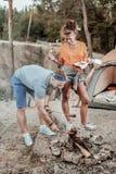 Ciemnowłosa dziewczyna pomaga jej mężczyzna obozu ogieniowi podpieka kiełbasy blisko zdjęcia stock
