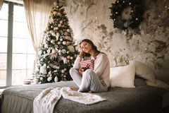 Ciemnowłosa dziewczyna siedzi na łóżku z szarość ubierał w białych puloweru i spodń chwytach nowego roku prezent w ona ręki fotografia stock