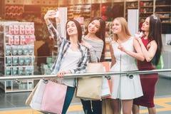 Ciemnowłosa dziewczyna w spodniach bierze obrazek ona z firmą Są w centrum handlowym Dziewczyny pozują niektóre i mają zdjęcia stock