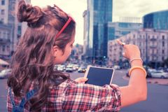 Ciemnowłosa dziewczyna z ładną włosianą babeczki pozycją, patrzeć ładnego centrum biznesu i zdjęcia royalty free