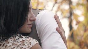 Ciemnowłosa kobieta ono uśmiecha się delikatnie i ściska mężczyzna w białej koszula w parku w jesieni popołudniu, zwolnione tempo zdjęcie wideo