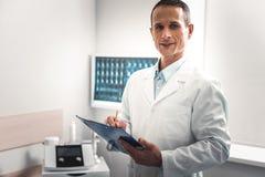 Ciemnowłosa lekarka robi niektóre znacząco notatkom zdjęcia royalty free