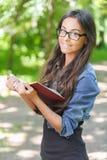 Ciemnowłosa młoda kobieta z książką Obrazy Royalty Free