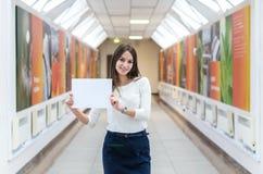 Ciemnowłosa studencka dziewczyna na kampusie trzyma pustego prześcieradło papier zdjęcia royalty free