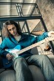 Ciemnowłosy baczny mężczyzna jest ubranym błękitną bluzę sportową i przygotowywa gitarę obrazy stock