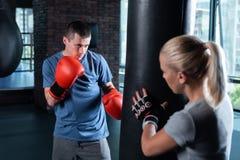 Ciemnowłosy bokser jest ubranym błękitnego koszulowego działanie z jego trenerem Fotografia Stock