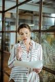 Ciemnowłosy ciężarny bizneswoman jest ubranym słuchawki w biurze obraz stock